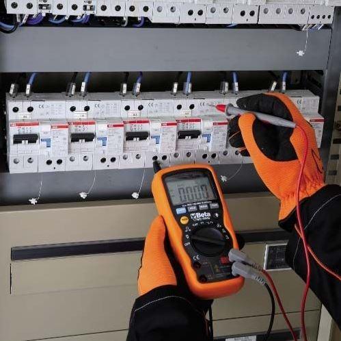 Electricien se servant d'un multimètre sur le compteur électrique